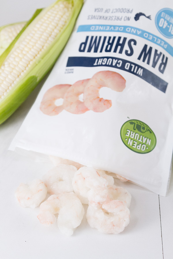 A bag of Open Nature Raw Shrimp open and the shrimp coming out of it with an ear of corn in the background