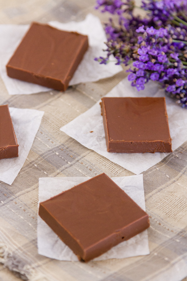 4 pieces of fudge on parchment paper on a cloth with lavender in the background