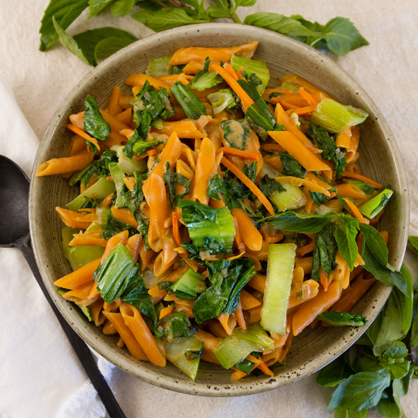 square crop of Thai Basil Pasta in a bowl with fresh basil leaves around