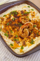Shrimp and cheese dip in a square clay baking dish with shrimp on top garnished with green onions