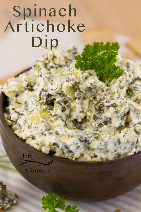 Spinach Artichoke Dip in a dark bowl with parsley on top. title on upper left of image