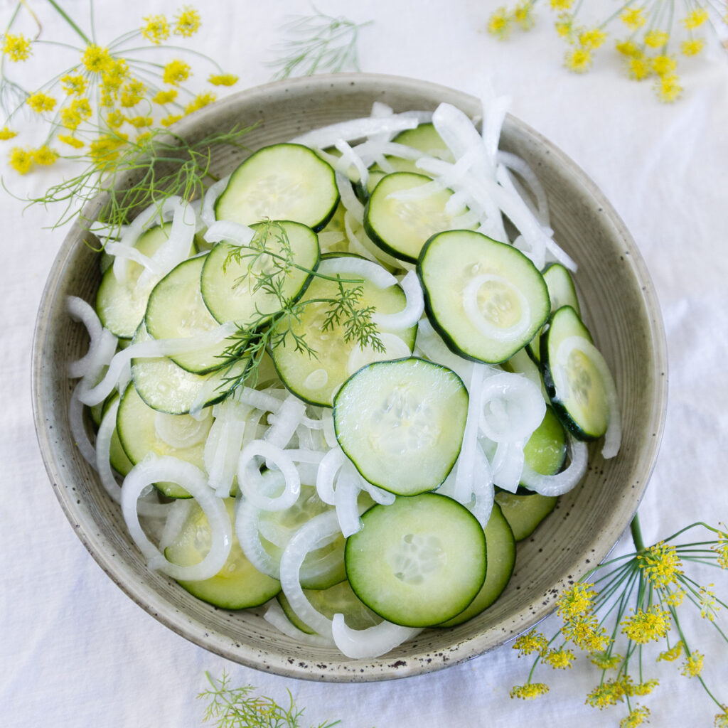square crop of salad in a bowl with dill flowers around it