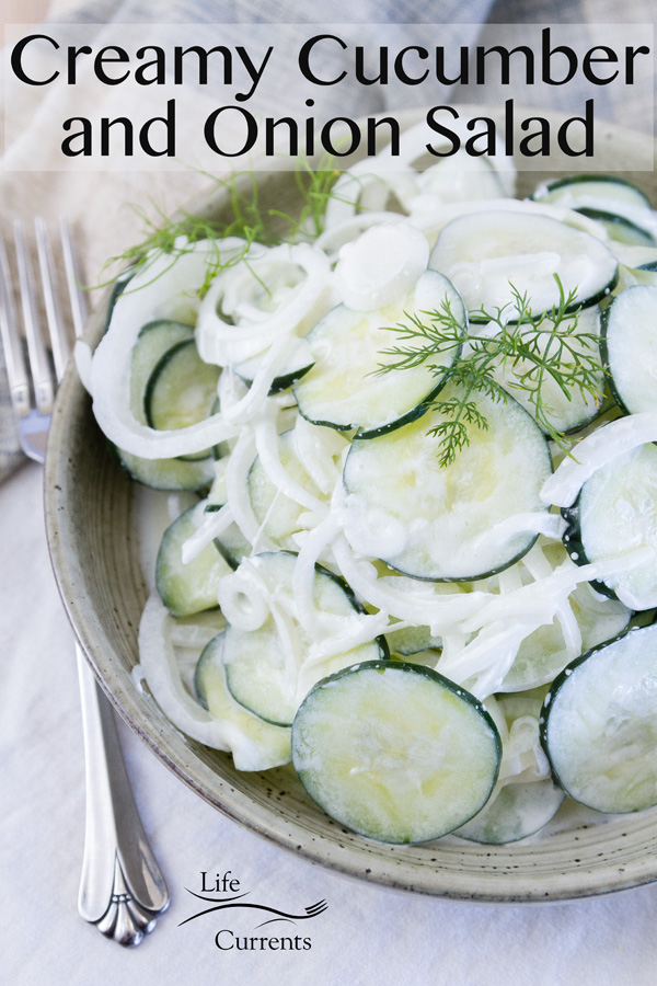 Creamy Cucumber and Onion Salad in a bowl with a fork. title on image