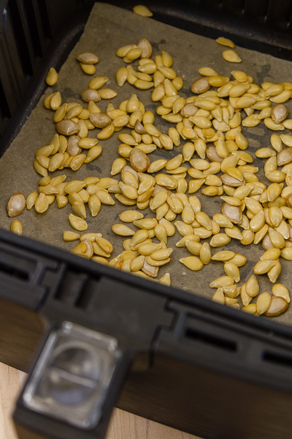 raw squash seeds in the basket of an air fryer