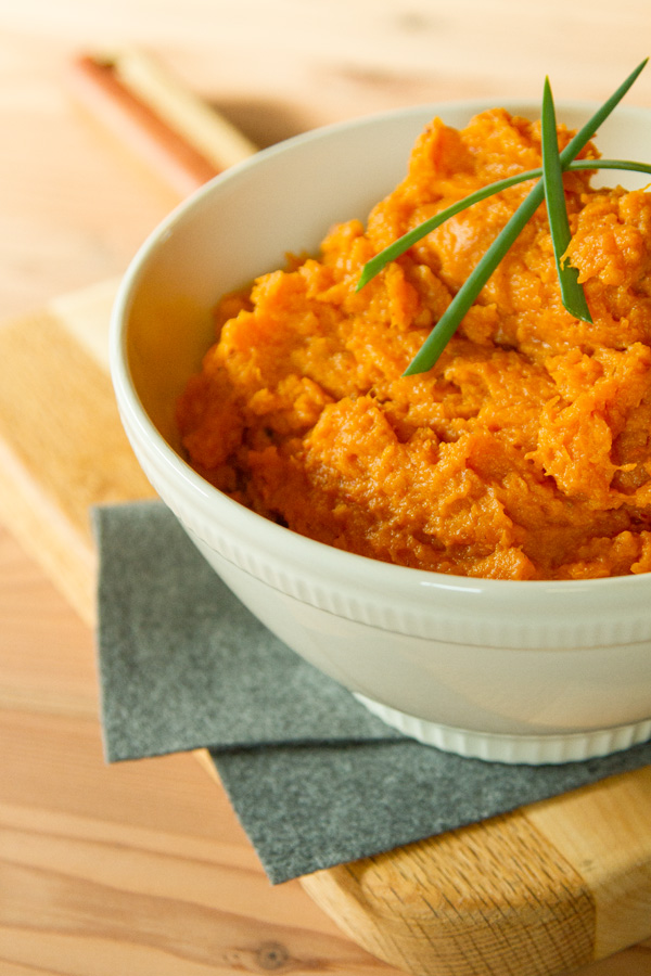 mashed sweet potatoes in a white bowl with 3 green onion pieces on top