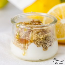 yougurt topped with wheat germ and honey with lemons and flowers in the background