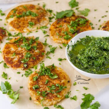 Several cooked potato patties that have been garnished with chopped cilantro served with a small bowl of Chimichurri.