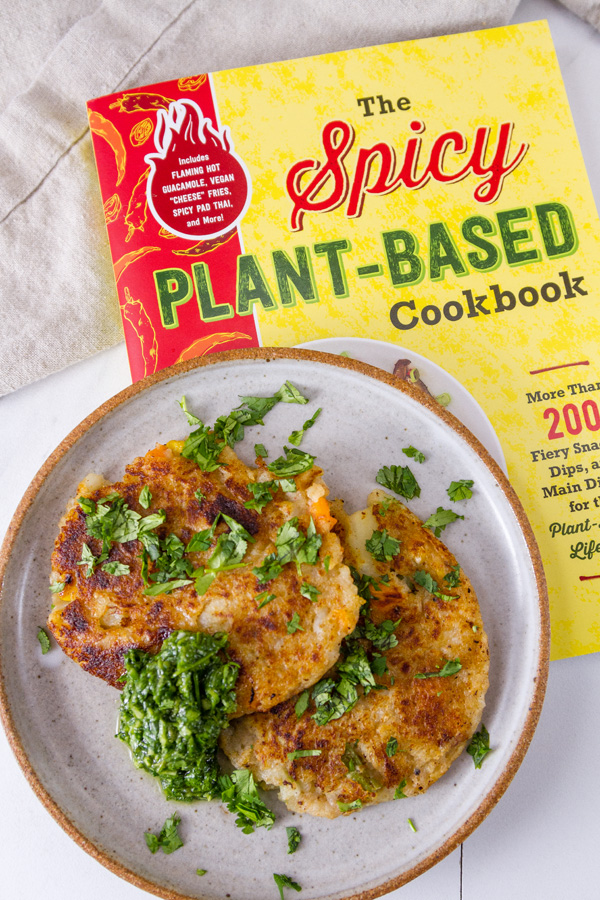 new cookbook, The Spicy Plant-Based Cookbook with potato fritters on a plate on top of the cookbook