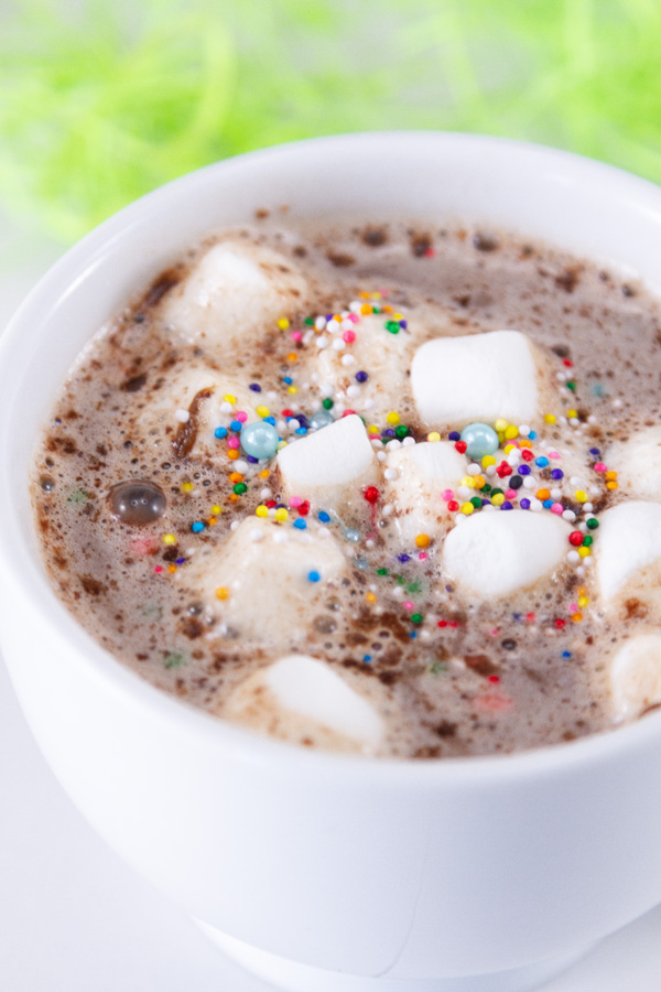 a mug of hot cocoa with marshmallows and sprinkles for Easter