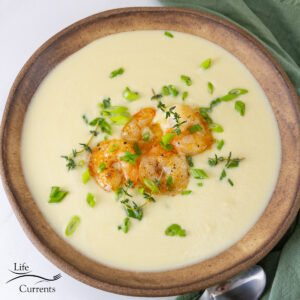 square crop of leek soup in a bowl with shrimp and herbs