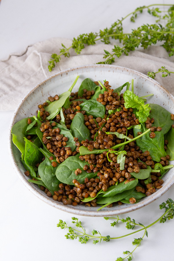 cooked lentils in a white bowl with fresh spinach leaves.