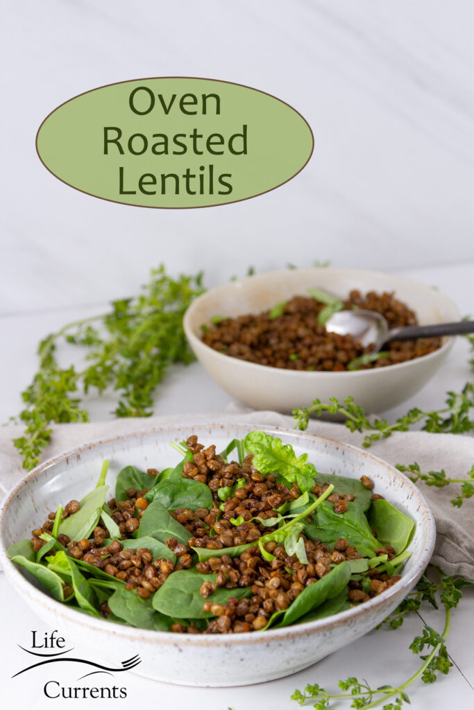 a white bowl filled with cooked lentils and spinach in front of a serving bowl with lentils and a spoon, fresh herbs around.