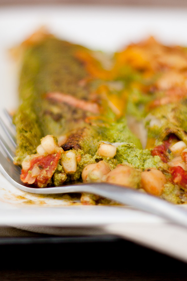 green enchiladas on a plate with a fork.