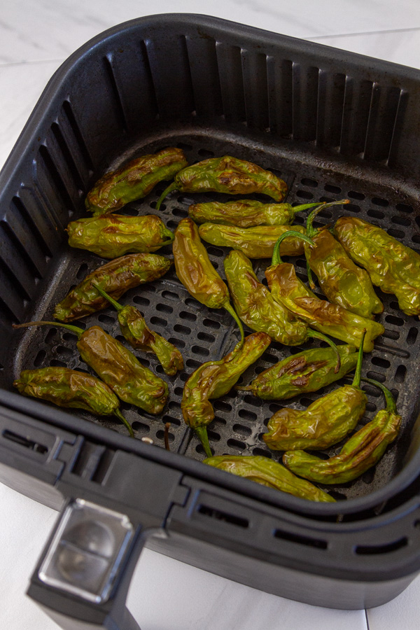 peppers in the basket of an air fryer.