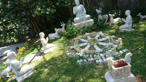 A marble statue garden - Buddha is accompanied by deers and praying monks. They all sit in a circle, around a dharmachakra wheel.