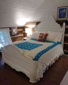 white bed frame with crocheted coverlet