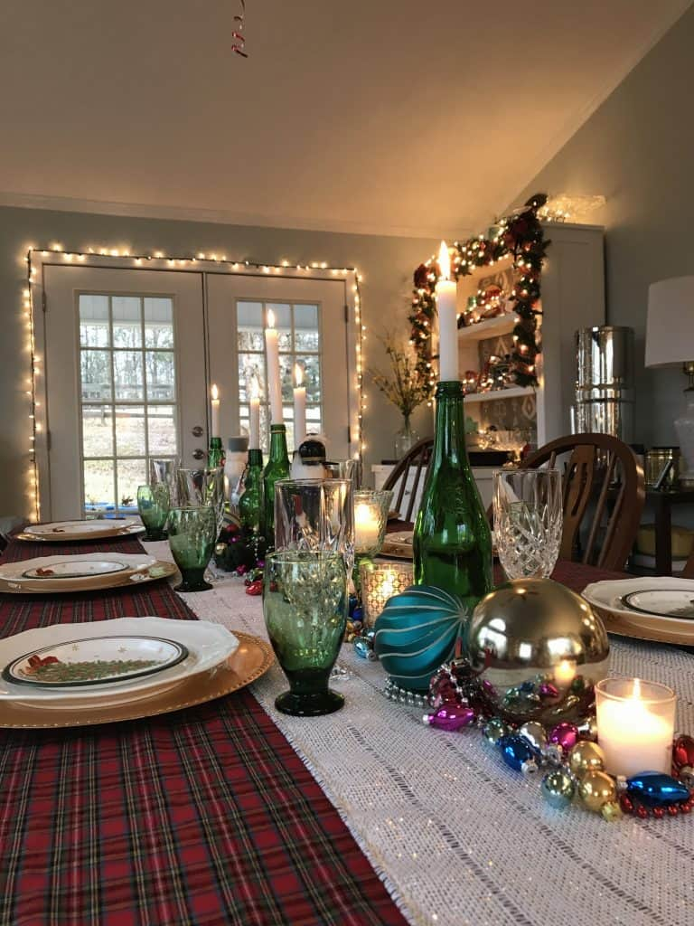 a Christmas table setting ready for Christmas dinner with a plaid table cloth, sparkling ornaments and lights and the glow of candles
