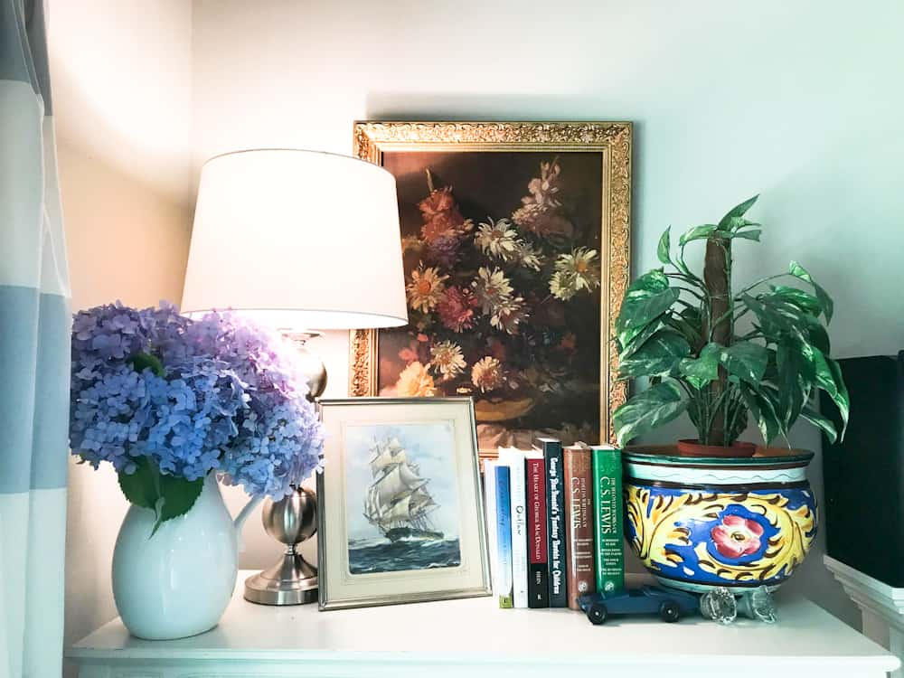 Life Full and Frugal / Summer Living Room Makeover / Top of Book shelf decorated with books, a vintage print of a ship on open water, a floral painting, a white vase with blue hydrangeas and a plant nestled in Mexican pottery