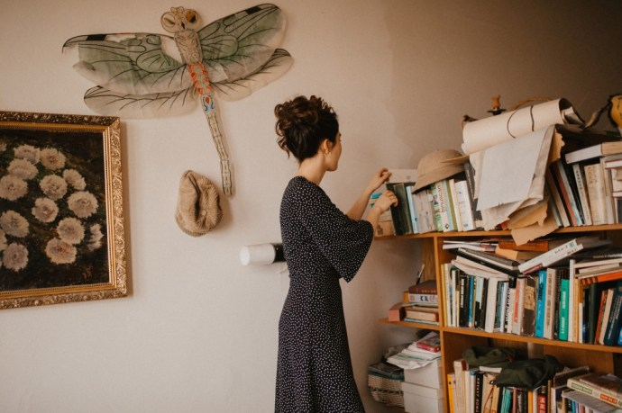 reading books on bookshelf as self-care for a high achiever type