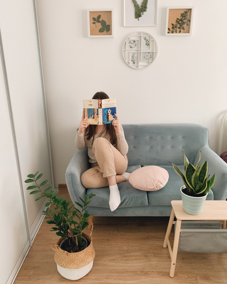 high achiever woman reading a book on couch in living room