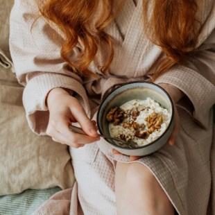 girl in robe eating breakfast on sunday morning