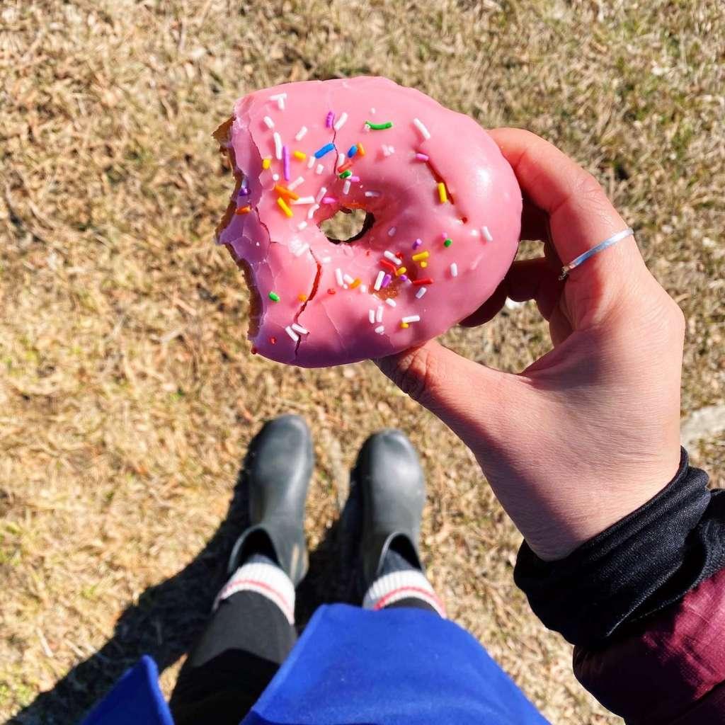 Girl holding a pink iced doughnut