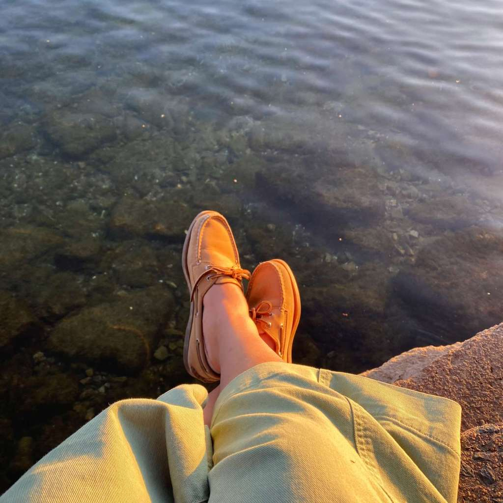 A top down view of someone sitting on a rock by the water, only their shoes are visible with a backdrop of water