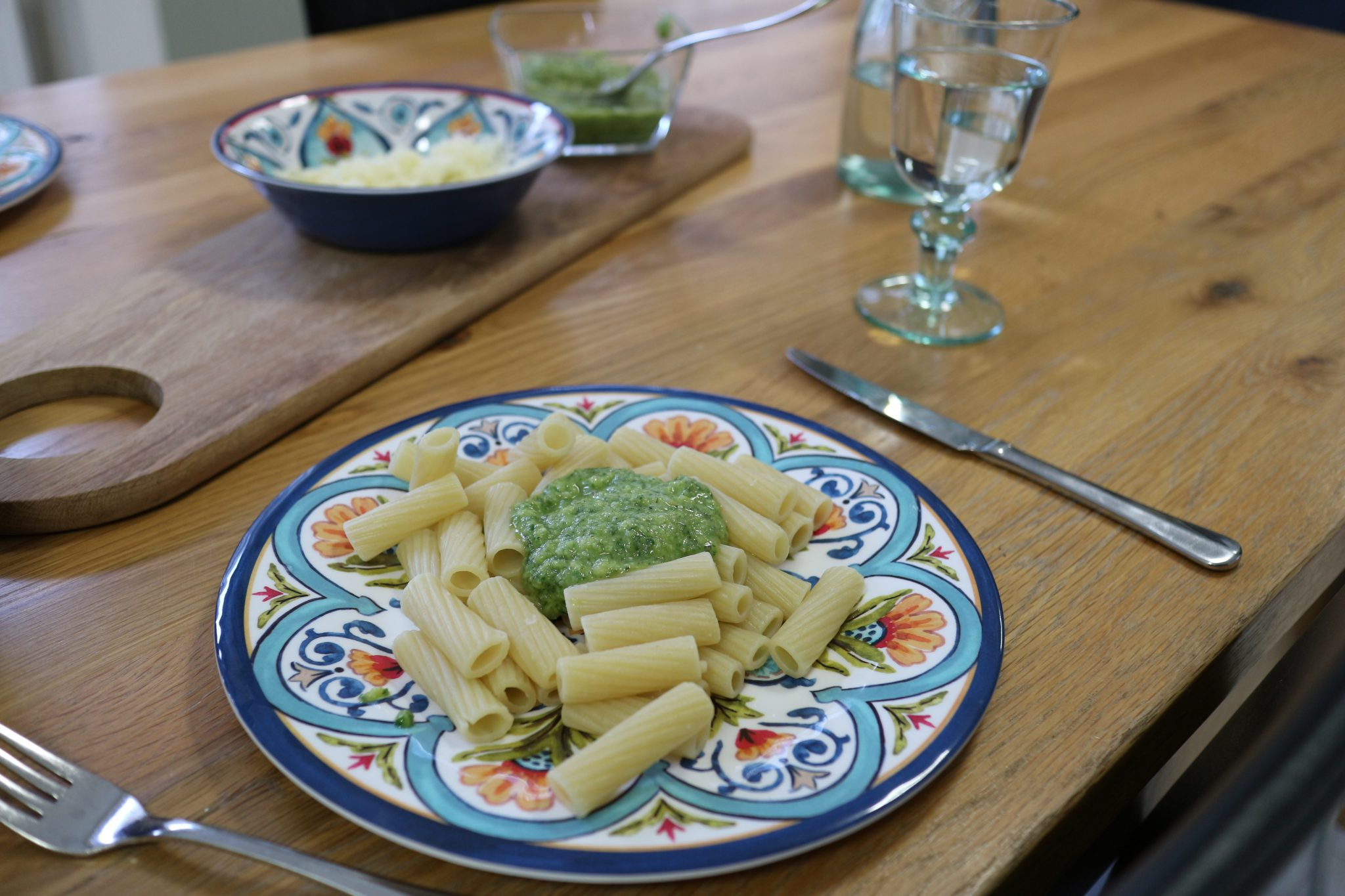A plate full of penne pasta and fresh basil pesto.