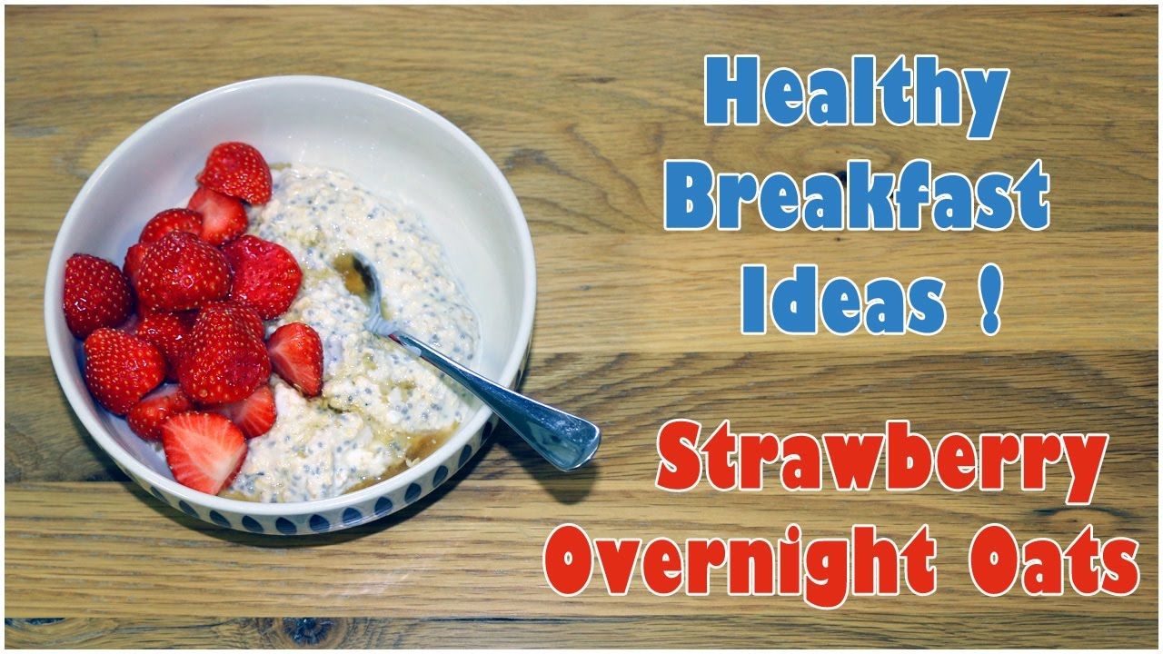 A bowl of overnight oats served with fresh strawberries and maple syrup.