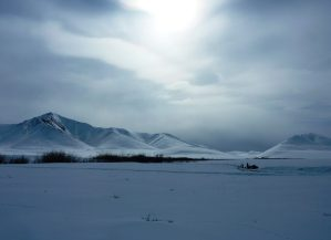 Snowscape of Alaskan Malamute sleddog team heads towards the Northern side of the Brooks Range, Alaska.