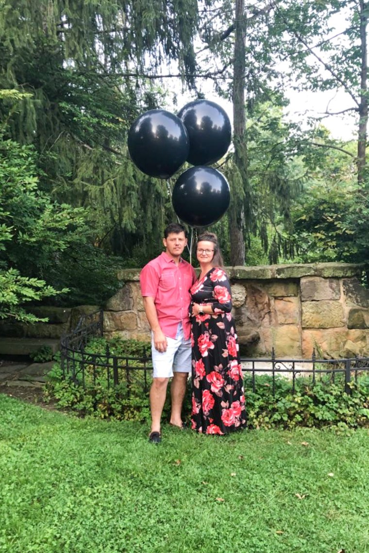 A couple standing holding black balloons for a gender reveal.
