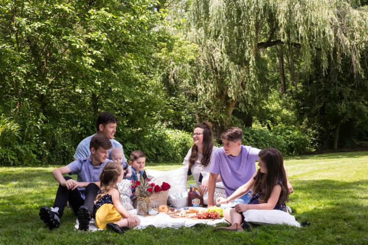 A family sitting on a rug outside having a picnic.