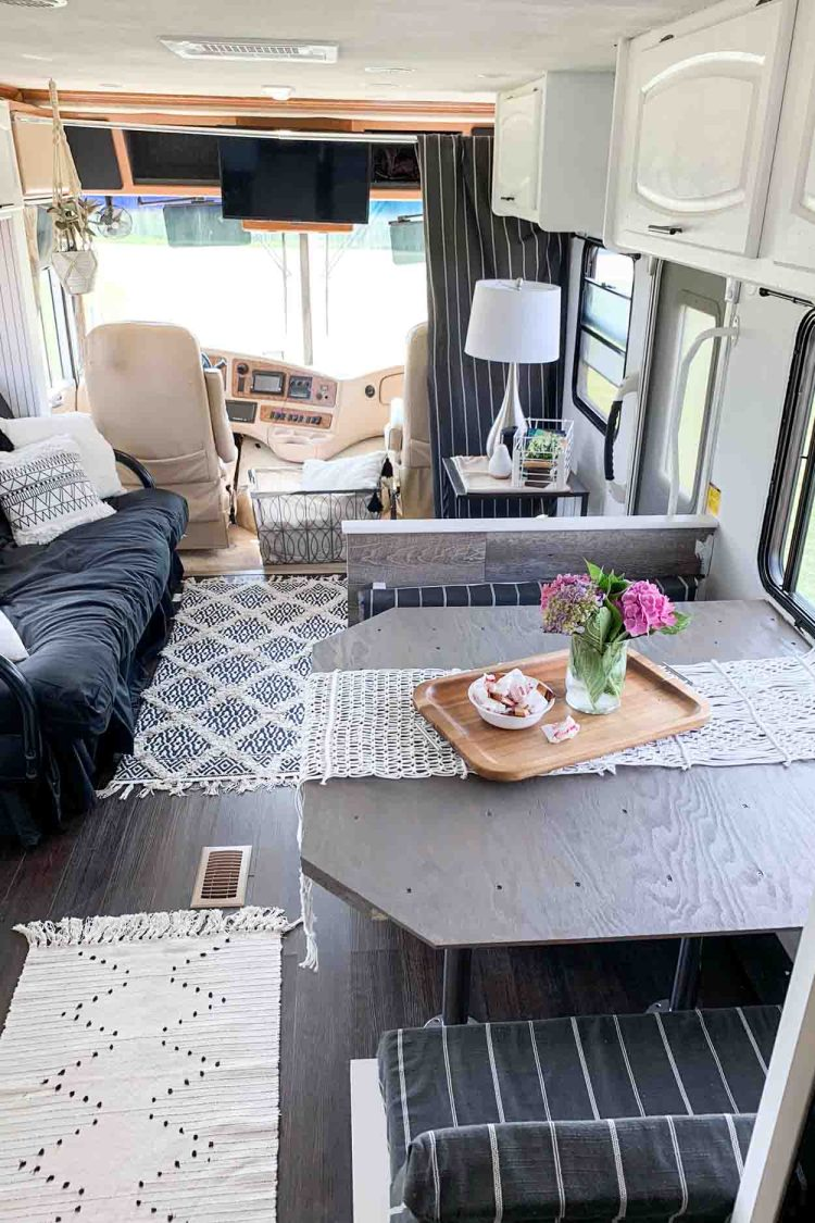 The front of the rv with a living space and the driver seat.