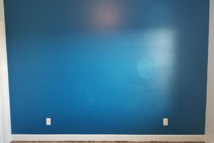 A blue wall that shows the before of the bedroom remodel.