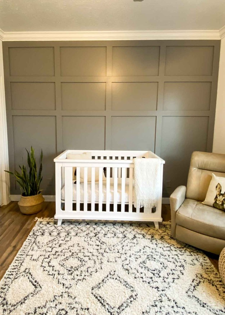 Nursery with gray wood accent wall with a white crib, plant and a rocking chair.