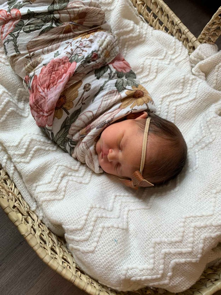 Baby Seraphima Ivy in a basket wrapped in a flower blanket and headband.