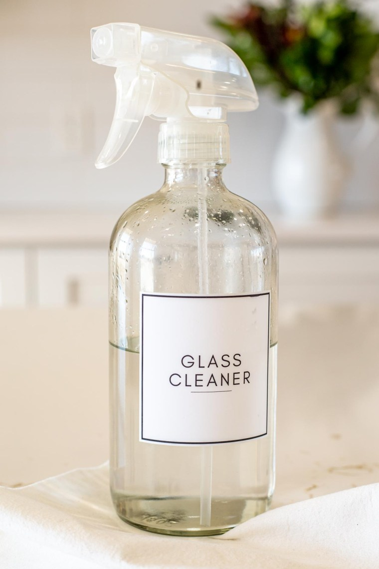 Glass bottle filled with homemade glass cleaner on a counter.
