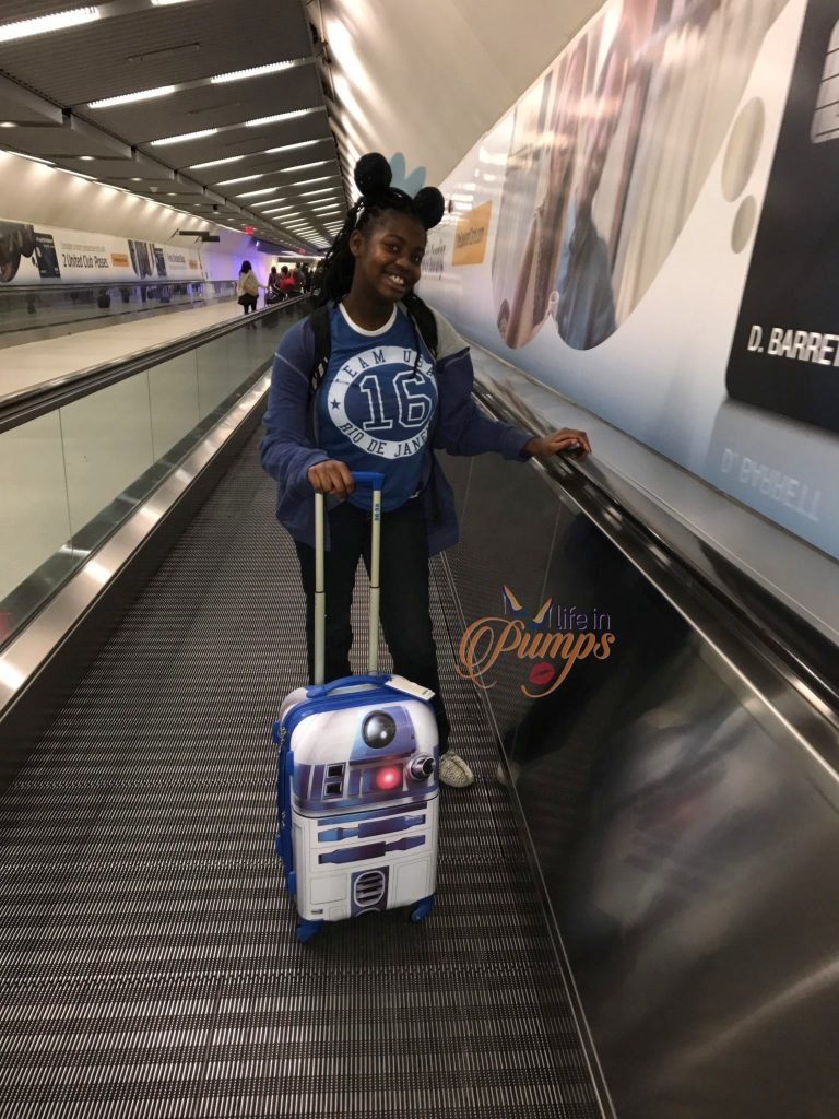 Brown Girl with Suitcase traveling to Disney World Pixie Dust