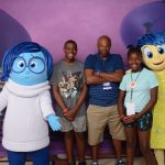 Brown kids at Disney World playing with characters from Inside Out