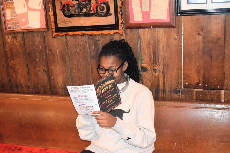 brown girl reading dinosaur bbq menu in Rochester NY
