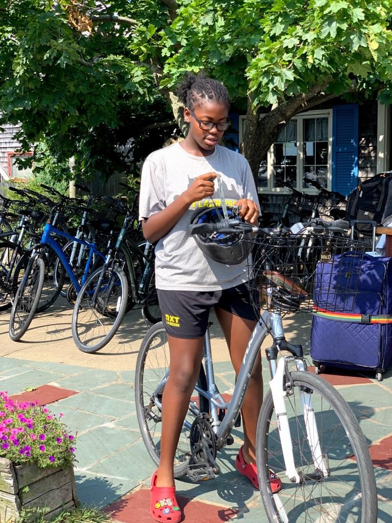 Brown girl biking in Marthas Vineyard sustainable travel