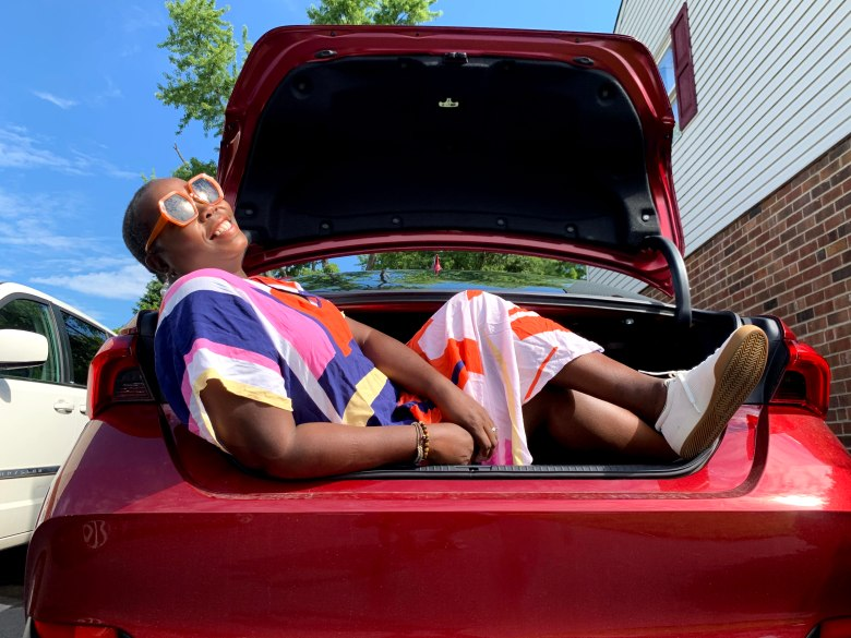 brown girl wearing kaftan with Roth's sneakers in trunk of 2021 Toyota Avalon hybrid