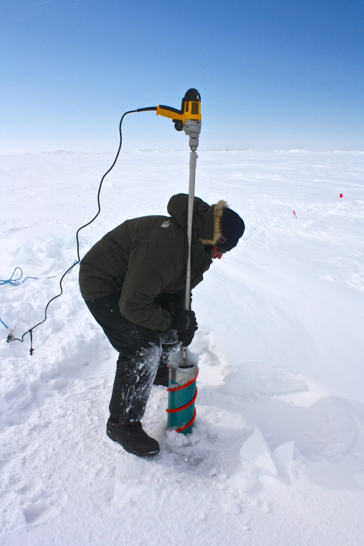 Craig Aumack uses an auger to drill an ice core.