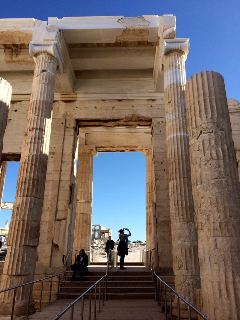 Entrance leading to the Parthenon. White marbled columns tower over the people.