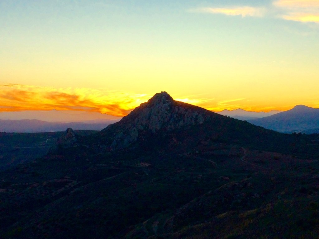 View of the orange sunset behind the mountain from the Acrocorinth carpark