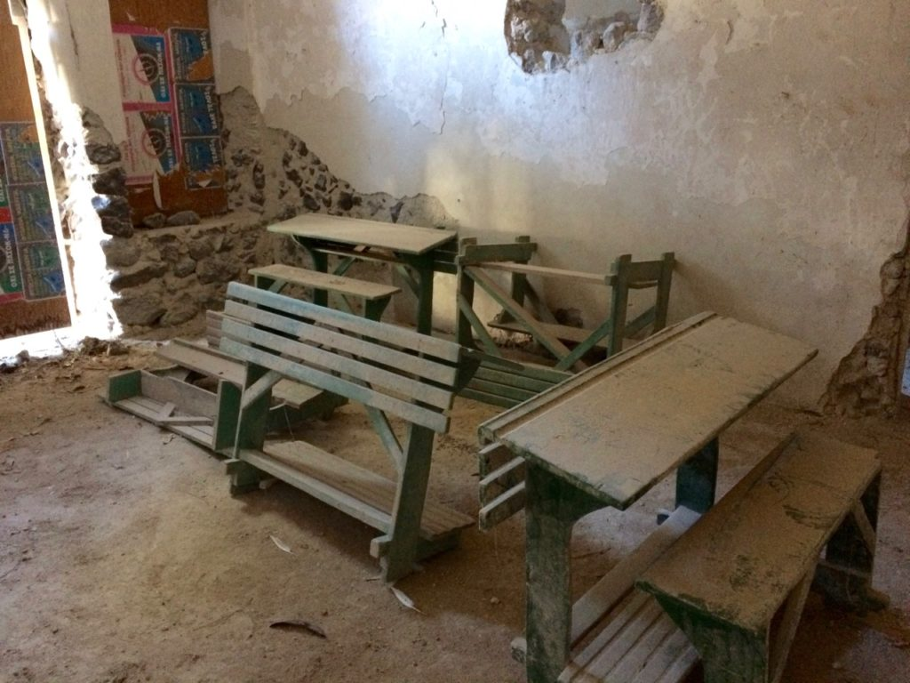 The dusty over turned green student desks in a dilapidated class room