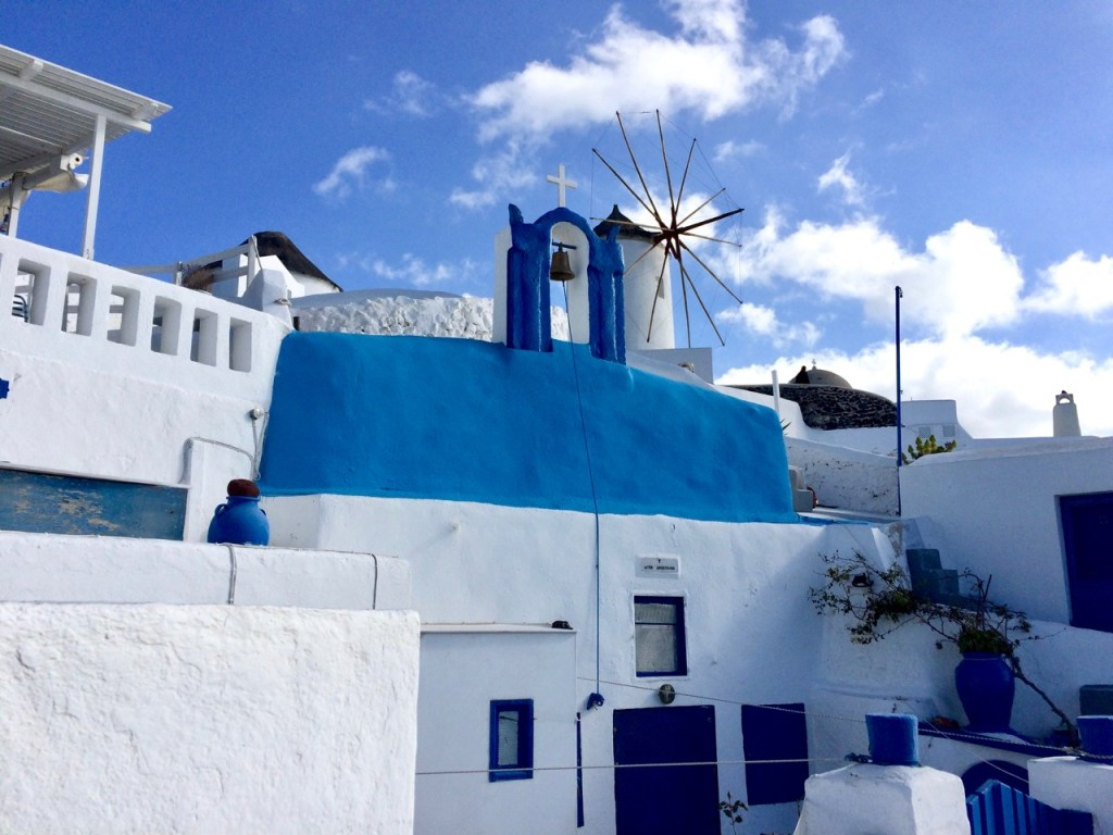 Vivid white-washed dwellings with the typical azure blue trimmings of Santorini showing a church and windmill in the background