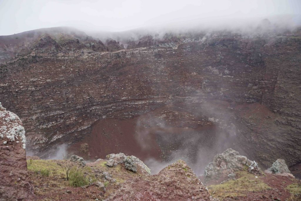 Steep brown crater walls with white clouds spilling over the rim