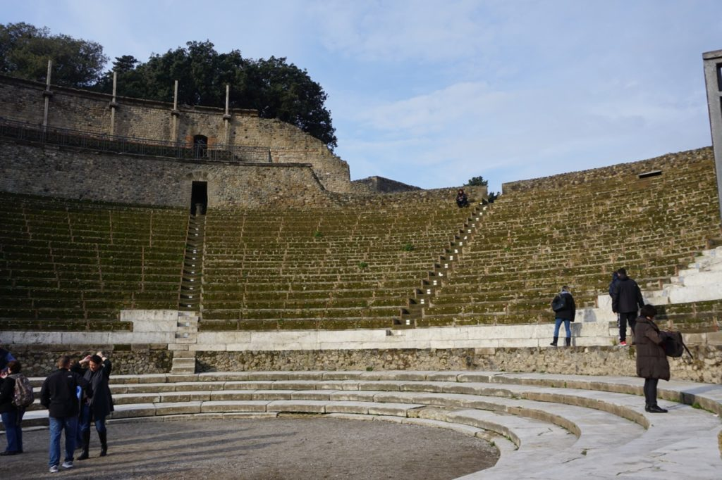 Stone amphitheatre with a large performance area at the bottom with surrounding stone columns on the perimeter