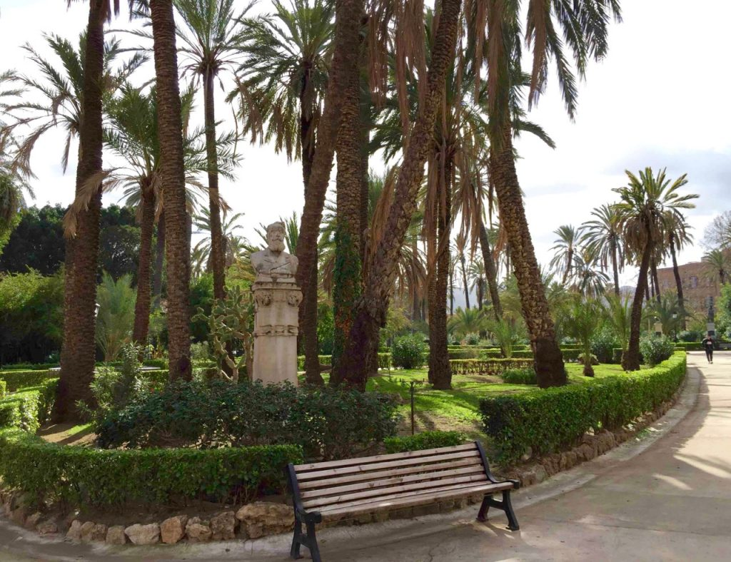 Giardino Garibaldi park with a bench, white statue and palm trees